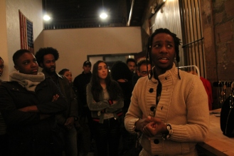 Featured Artist Pharaoh Darrell explaining his paintings on display at the MO listening party